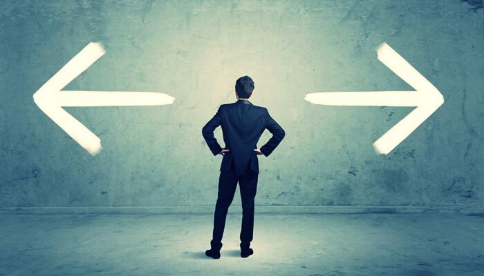左右に伸びる矢印の前で立っている男性